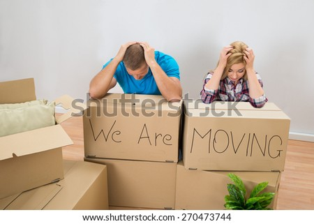 Frustrated Young Couple With Moving Boxes At Home - stock photo