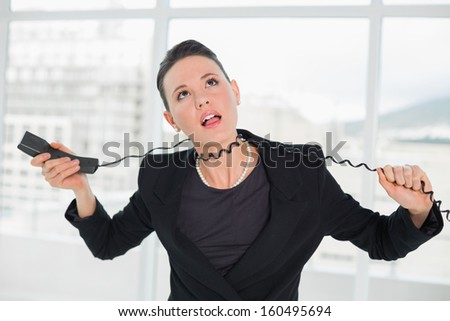 Frustrated young elegant businesswoman with telephone cable around her neck at a bright office - stock photo
