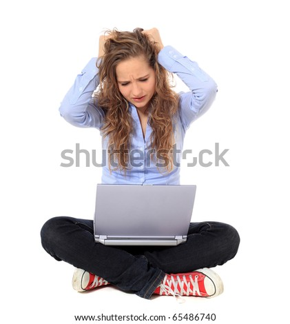 Frustrated young girl using notebook computer. All on white background. - stock photo