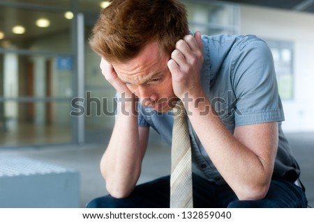 Frustrated young, handsome businessman at office - stock photo