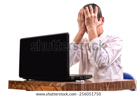 Frustrated young man, holding his head in front of a laptop in the classroom - stock photo