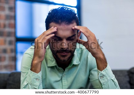 Frustrated young man sitting on sofa in the office - stock photo