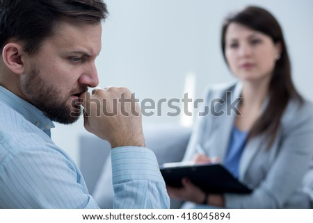 Frustrated young man with depression at psychotherapist's office