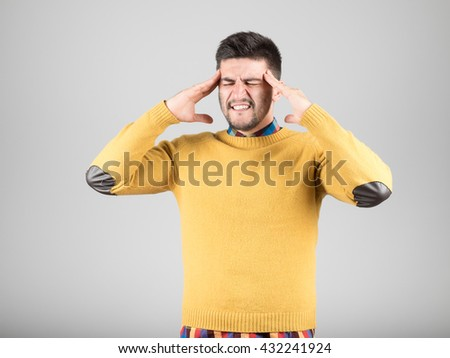 Frustrated young man with headache isolated over gray background - stock photo