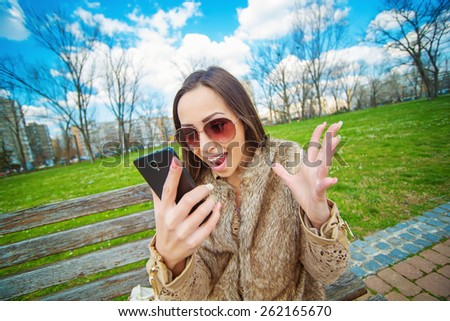Frustrated young woman at park yelling on her smart phone. Bad conversation, bad connection.  - stock photo