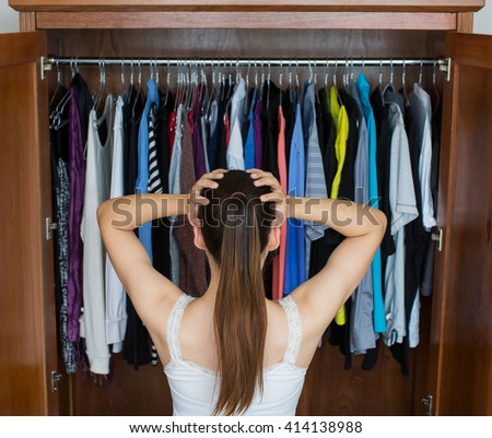 Frustrated young woman cannot decide what to wear from her closet - stock photo