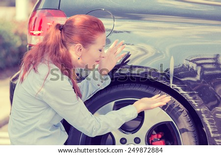 Frustrated young woman checking pointing at car scratches and dents outdoors outside  - stock photo