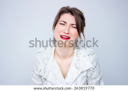 Frustrated young woman screaming  in the white  elegant jacket , suit the makeup red lipstick - stock photo