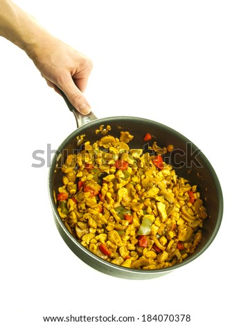 Fry pan with chicken with curry, red pepper and corn held by a male chef towards white background - stock photo