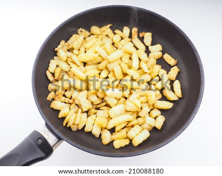 Frying chopped potatoes in a fry pan isolated - stock photo
