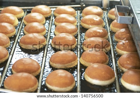 Frying Donuts In Hot Grease On Conveyor - stock photo