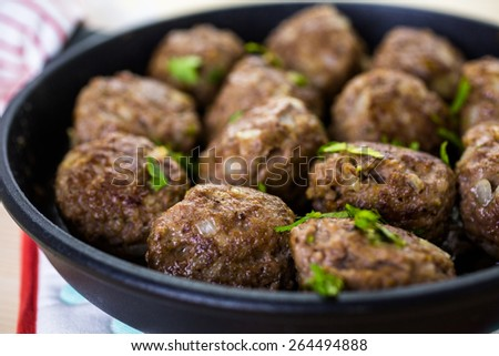 Frying large homemade Italian meatballs on a midium frying pan for dinner. - stock photo