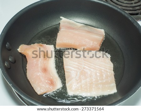 Frying mahi mahi fillet in oil on large pan - stock photo