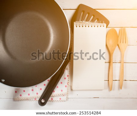 frying pan and blank recipe book with wooden spoon - stock photo