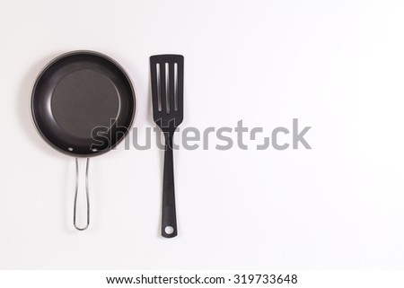 frying pan and spatula with copyspace isolated on white background - stock photo