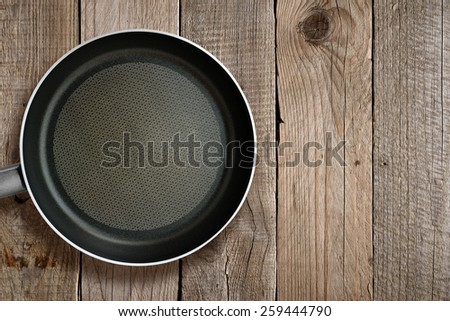 Frying pan on wooden background - stock photo