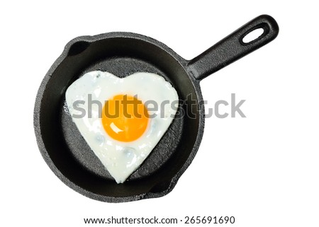 Frying pan with fried egg in shape of heart isolated on white background - stock photo