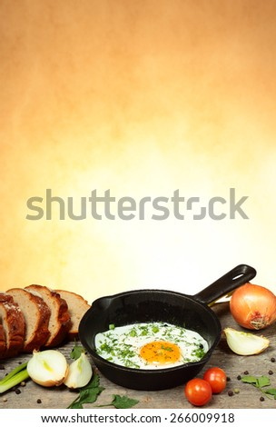 Frying pan with fried egg on old wooden table with abstract background - stock photo