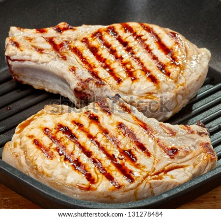 Frying pan with grilled steak. - stock photo