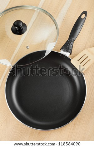 frying pan with lid on wooden table - stock photo