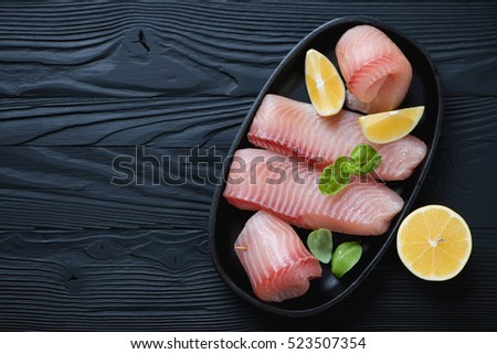 Frying pan with marinated tilapia over black wooden background, above view, copyspace