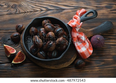 Frying pan with roasted chestnuts in a rustic wooden setting