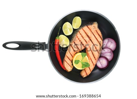 Frying pan with salmon steak. Isolated on a white background. - stock photo