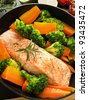 Frying pan with salmon steak, stir-fry veggies and herbs, Shallow dof. - stock photo