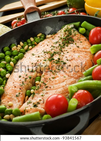Frying pan with salmon steak, stir-fry veggies and herbs. Viewed from above. - stock photo