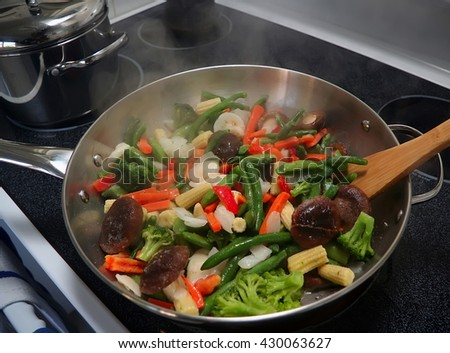 Frying pan with stir fry vegetables at hot  stove top