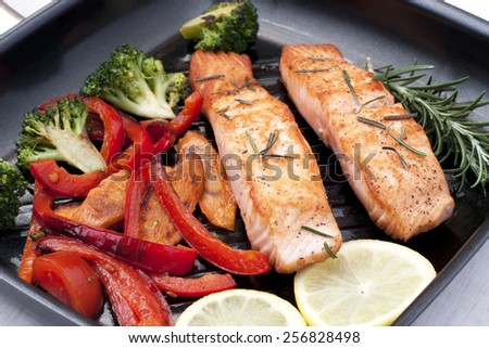 Frying pan with two salmon steaks and vegetables