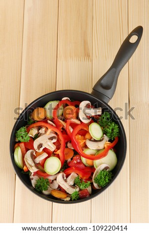 frying pan with vegetables on wooden background - stock photo