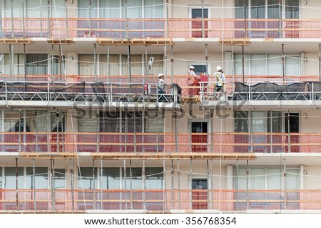 FT LAUDERDALE, FLORIDA - NOV 23, 2010:  Construction workers standing on scaffolding, renovating an apartment building in Ft Lauderdale, Florida on November 23rd, 2010. - stock photo