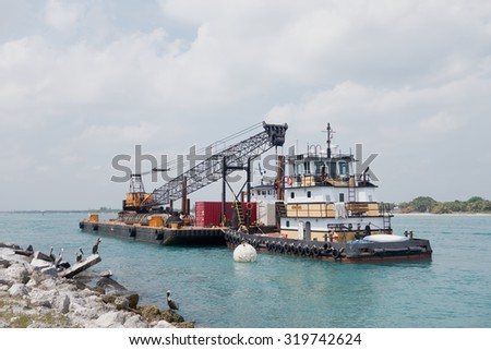 Ft. Pierce, FLORIDA - March 22, 2015: Floating barge and crane working on the repair on the wall and basalt blocks of the Ft. Pierce inlet in Florida - stock photo
