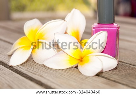 Fuchsia nail polish in the bottle and flowers on the woody background