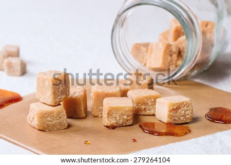 Fudge candy and caramel on baking paper and in glass jar, served over white tablecloth with jar of brown sugar - stock photo
