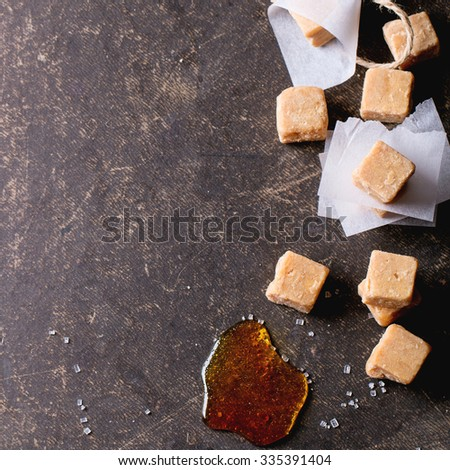 Fudge candy and caramel on baking paper, served with thread over dark background. Top view. Square image - stock photo