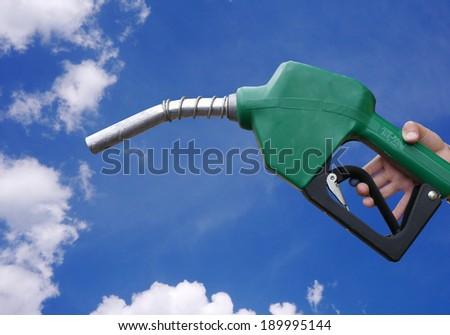 Fuel dispenser on blue sky background. - stock photo