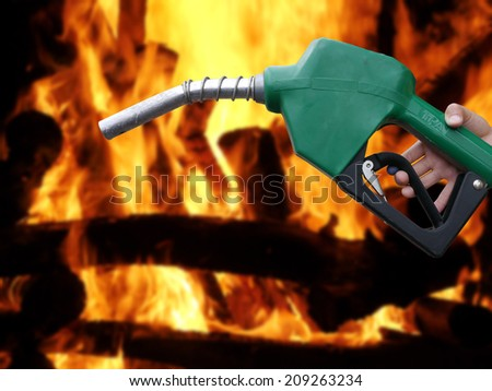 Fuel dispenser on fire background - stock photo