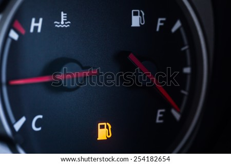 Fuel Gauge Showing Almost Empty, Red warning icon light. - stock photo
