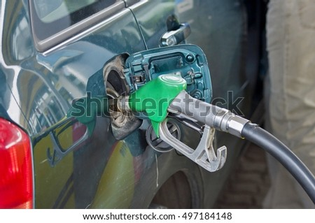Fuel nozzle add a fuel to a car on a petrol station.