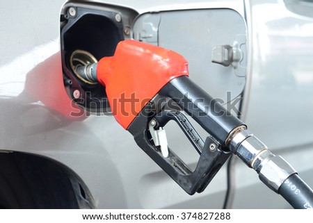 Fuel nozzle add fuel in car at gas station. select focus