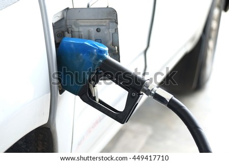 Fuel nozzles adding fuel in the car at gas station - stock photo