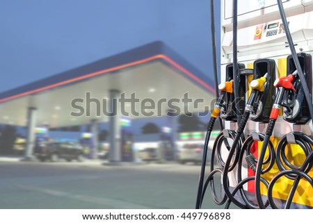 Fuel oil dispenser with petrol filling station blurry background - stock photo