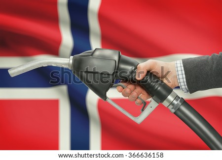 Fuel pump nozzle in hand with flag on background - Norway