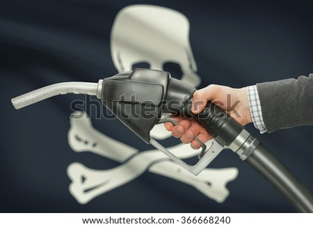 Fuel pump nozzle in hand with flags on background series - Jolly Roger - symbol of piracy - stock photo