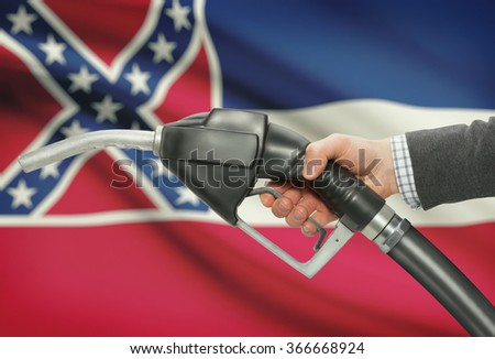 Fuel pump nozzle in hand with US states flags on background - Mississippi