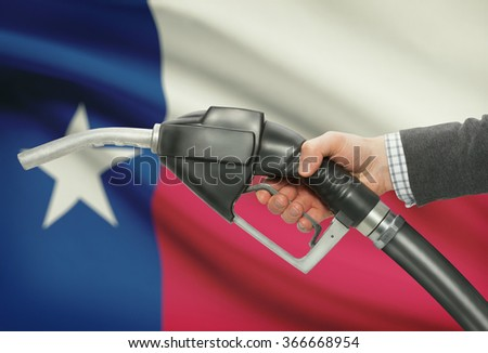 Fuel pump nozzle in hand with US states flags on background - Texas - stock photo