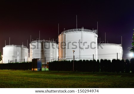 Fuel storage tanks at oil terminal by night