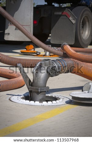 Fueling truck with drop hose connected to underground fuel tank - stock photo